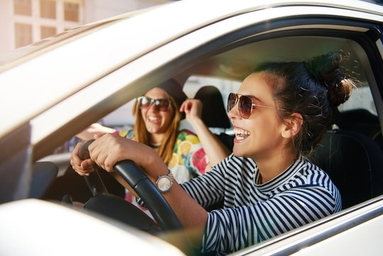 Two laughing young girlfriends driving on a road trip together