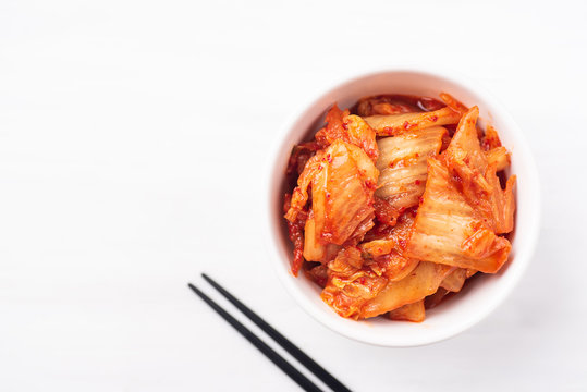 Kimchi cabbage in a bowl with chopsticks on white background, top view, Korean food