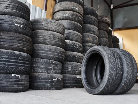 Used car tires stacked in piles at tire fitting service. Wheels for repair shop. Car service concepr