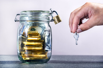 Businessman holding keys from container with currency. Finance Savings concept