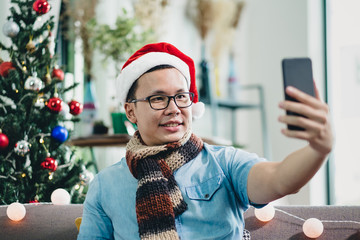 asian man smile and  take selfie photo with mobile phone with blur christmas tree at xmas party,Live streaming video on social media event,Christmas holiday celebration party.