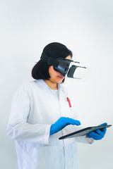 Portrait of woman scientist is using tablet while wearing virtual reality glasses in laboratory room