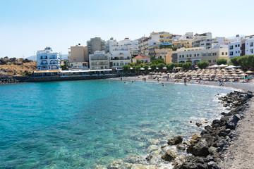 Agios Nikolaos. Crete. Vacationers on the beach at the waterfront Akti PapaNikolaou Pagkalou