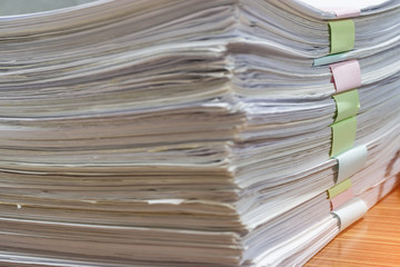 Close up pile of unfinished homework assignment stacked in archive with colorful papers on teacher's table waiting to be managed and inspected. Stack of  paperworks. Education and business concept.