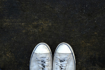 Top view of old canvas shoes on cement floor background