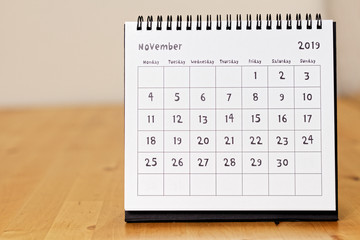 Month page: November in 2019 paper calendar with funny font on the wooden table