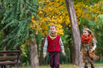Happy children play and run in autumn park