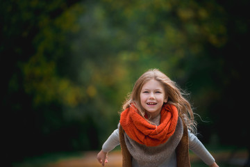 Positive little girl covered in plaid in the autumn park