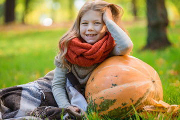 Little girl with large pumpkin outdoor in autumn park