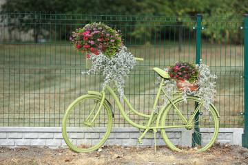 Rower seledynowy z kwietnikiem, różowe i czerwone kwiaty.