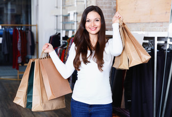 Young woman with bags happinnes from purchases in the clothes shop