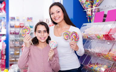 Smiling female and girl with lollipop in sweet-shop