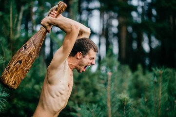 Fototapeta Odd primitive naked man with huge wooden stick hunting in forest. Adult male have fun like crazy psyche with rude club in hands. Expressive excited boy face.  Wild masculine strength. Cruel warrior.