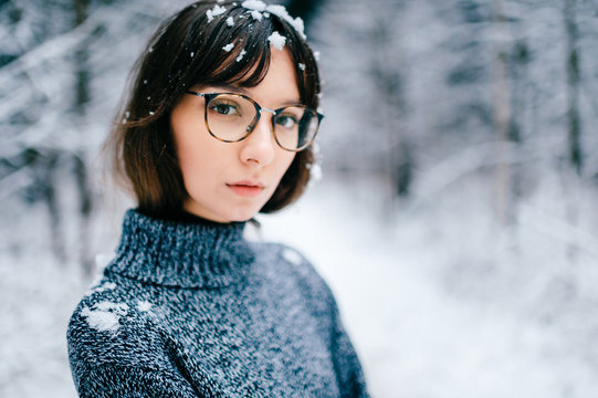 Young odd beautiful adorable lovely girl in knitted sweater portrait outdoor in cold winter forest. Fashionable model in trendy glasses with snow covered hair bang freezing. Nice looking woman face.