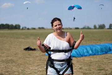 Wesoła i radosna dziewczyna po wylądowaniu na spadochronie.