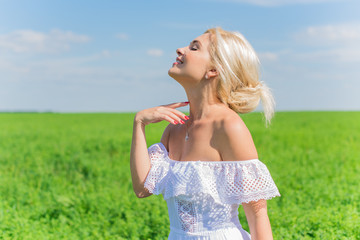 Freedom concept. Sweet happy woman in green field, evening light. Blue sky behind. Beauty Girl Outdoors enjoying nature. Beautiful Model girl in linen dress on the meadow