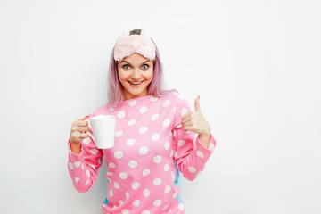Good Morning. Smiling young woman shows thumb up. Girl in pink pajamas and sleep mask