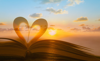 Book heart against beautiful sunset.Reading, love, romance and religion concept. Double exposure.