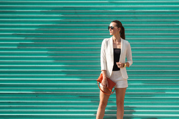 Attractive fashionable female posing against garage door.
