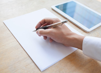 Businessman's hand writing on blank piece paper.