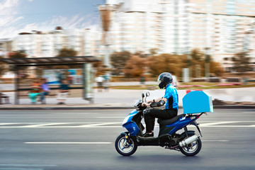 Delivery boy of takeaway on scooter with trunk case box driving fast in rush. Courier delivering food by scooter to avoid traffic jams. Wall mural