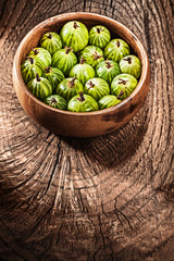 Gooseberries in round bowl on vintage wooden background