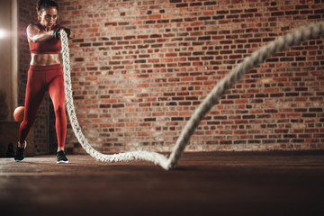 Tough woman exercising with battling rope