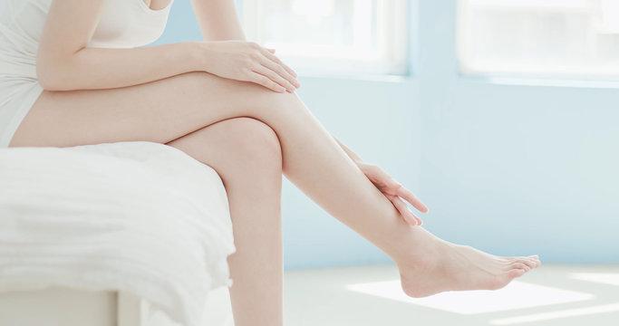 woman apply cream with leg