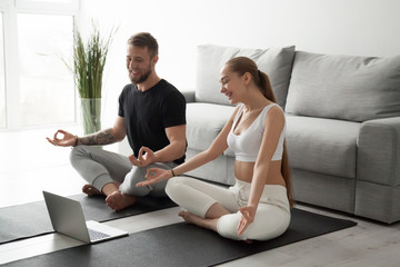 Garden Poster Lotus flower Smiling millennial couple practice yoga on mats at home watching video tutorial on laptop, excited man and woman sit in lotus position meditating repeating online instructions by coach on computer
