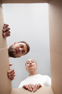 Funny millennial couple looking inside received cardboard parcel, frustrated clients or customers disappointed with delivered box with wrong order or damaged product. Bad delivery service concept
