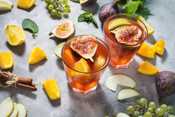 Cocktail fruit sangria with apples, orange, figs, grapes on concrete table