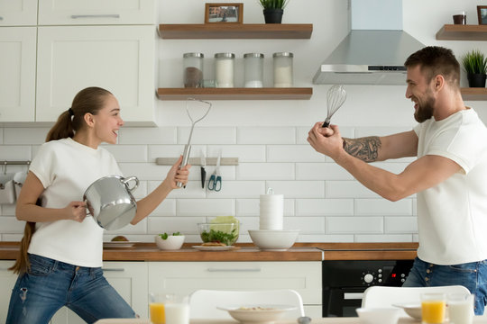 Happy young couple having fun in kitchen playing with kitchenware while preparing breakfast, playful millennial man and woman cooking food at home together involved in imaginary fight with utensils