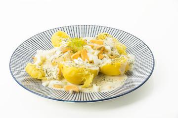 Dillkartoffeln, gekochte Kartoffeln, Dill-Rahm-Sauce und gekochte Eier, serviert auf einem blauen Teller auf weissen Untergrund, Freisteller