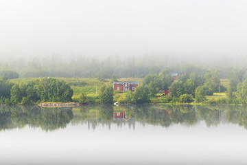 Old farm at a mirrored lake with morning mist