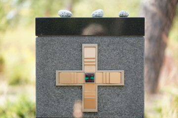 Ritual: drei Kuieselsteine auf Grabmal mit Kreuz