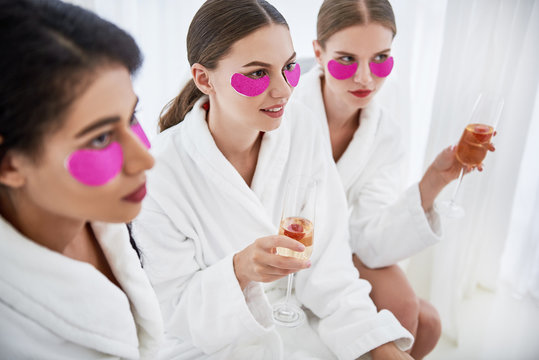 You have my attention. Young ladies with cosmetic masks holding glasses of champagne. They wearing bathrobes and listening someone with interest