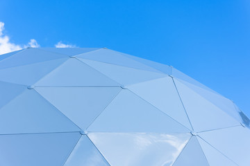 Dome consisting of triangular pieces of shelter section on the sky background.