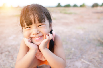 Asian children poor or kid girl smile with laugh and happy fun because come back home to country and wear traditional top or sleeveless shirt sit on arid soil for agriculture at home and warm sunlight