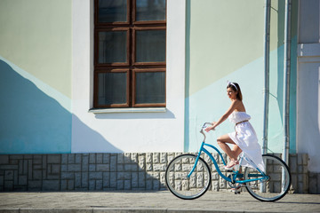 Refined woman is riding a blue vintage bike in a hot summer day in the city streets. Summer white dress develops a light breeze and an accessory on her head adds romanticism to the landscape