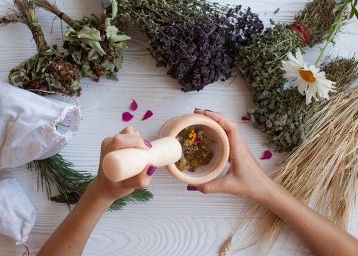 Grinding dried herbs with a mortar and pestle
