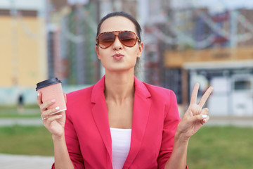 A pretty girl in sunglasses and a Cup of coffee in her hand shows a peace sign and sends a kiss. Lifestyle and positive emotions outdoors