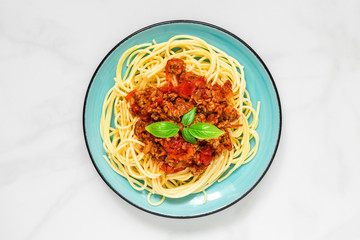 Spaghetti bolognese on a blue plate on white marble table. healthy food. top view