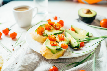 served light table with breakfast of sandwiches with avocado and cherry tomatoes and a cup of coffee