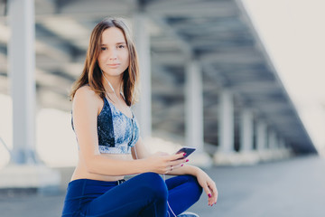 Photo of pleasant looking attractive sporty woman sits crossed legs, dressed in top and leggings, holds modern cell phone, enjoys lively music in earphones, poses outdoor. Entertainment concept