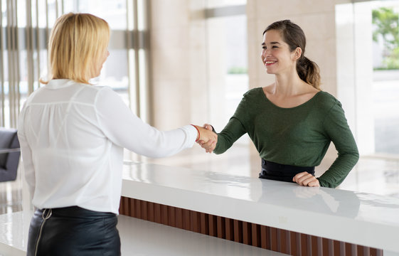 Office receptionist greeting corporate partner with handshake. Woman in formal clothing shaking hands over reception counter. Partnership concept