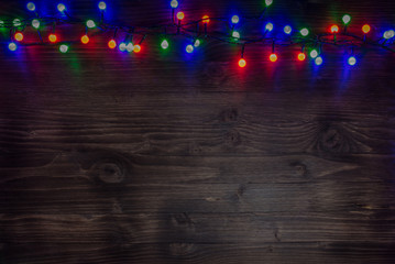 Colorful fairy lights on wooden background