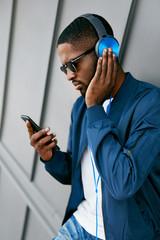 Man Listening Music In Headphones On Phone In Street.