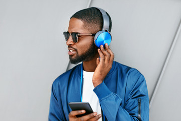 Listen Music. Man With Headphones And Phone In Fashion Clothes