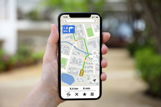 female hand holding phone with app navigation map on screen