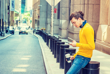 Working Break. Young Hispanic American with hair bun, wearing glasses, yellow long sleeve T shirt, blue jeans, small black scarf around neck, holding cup of coffee, sitting on street, texting..